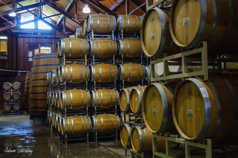 Dozens levels of barrels of wine stored horizontally. The barrels hold 60-gallons of wine, except for two which are over 12 feet tall and 8 feet around. There is a wet concrete floor with a large window near the cieling.